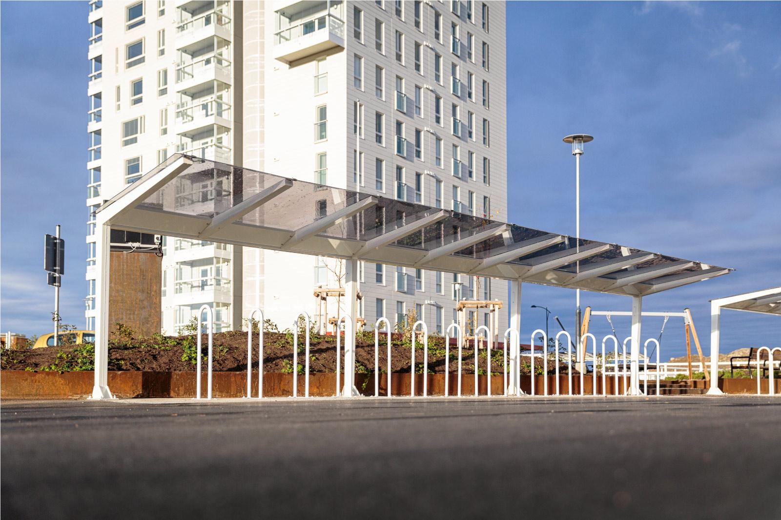 Light pyöräkatos lasin tunteella, neliskulmaiset putket ja katos polykarbonaattia, viimeistely pyöräkatos muotoilullaan, katoksen kanssa voidaan yhdistää runkolukitusteline. Light valkoisilla kattotuilella, kuvan katos Oulusta