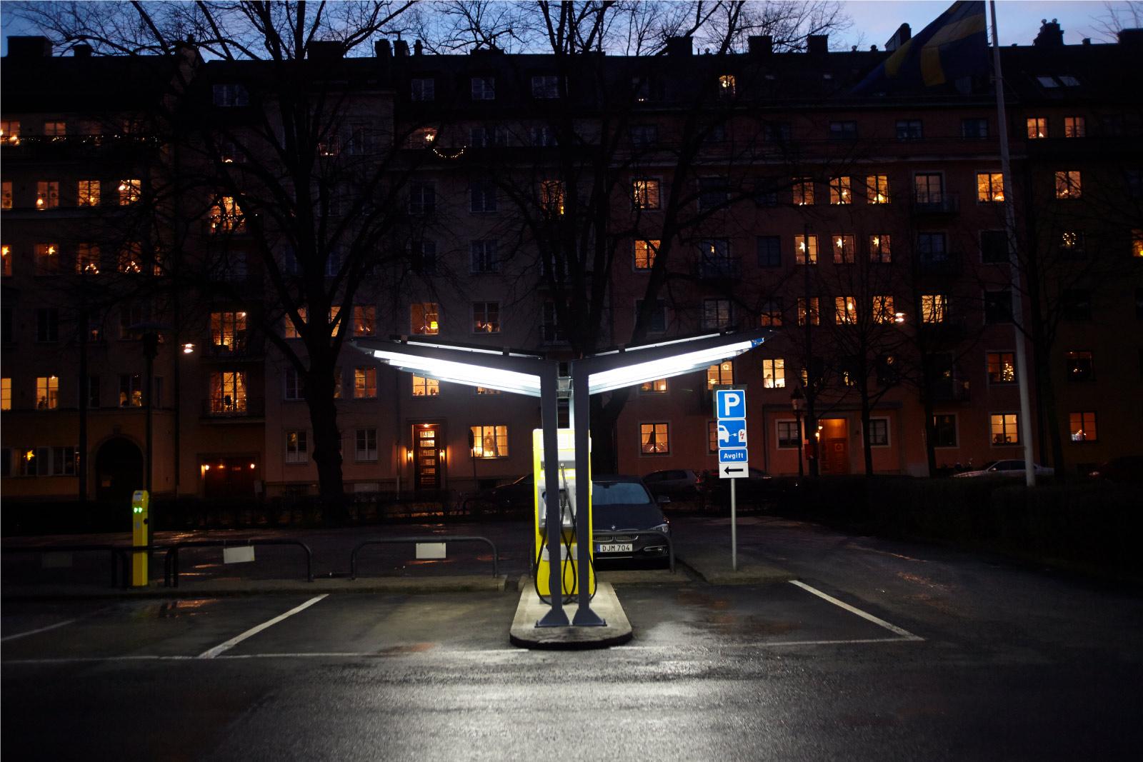 sunlight sääsuoja joss aurinkokennot katoksen päällä, latausasema sähköautoille, kuva iltahämärässä ja valistuksen kanssa