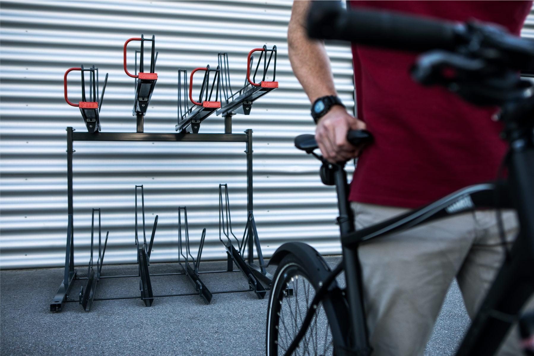Cyklos OPTIMA kaksikerros pyöräteline. 2-kerros teline runkolukituksella, henkilö kävelee pois telineestä pyörän kanssa