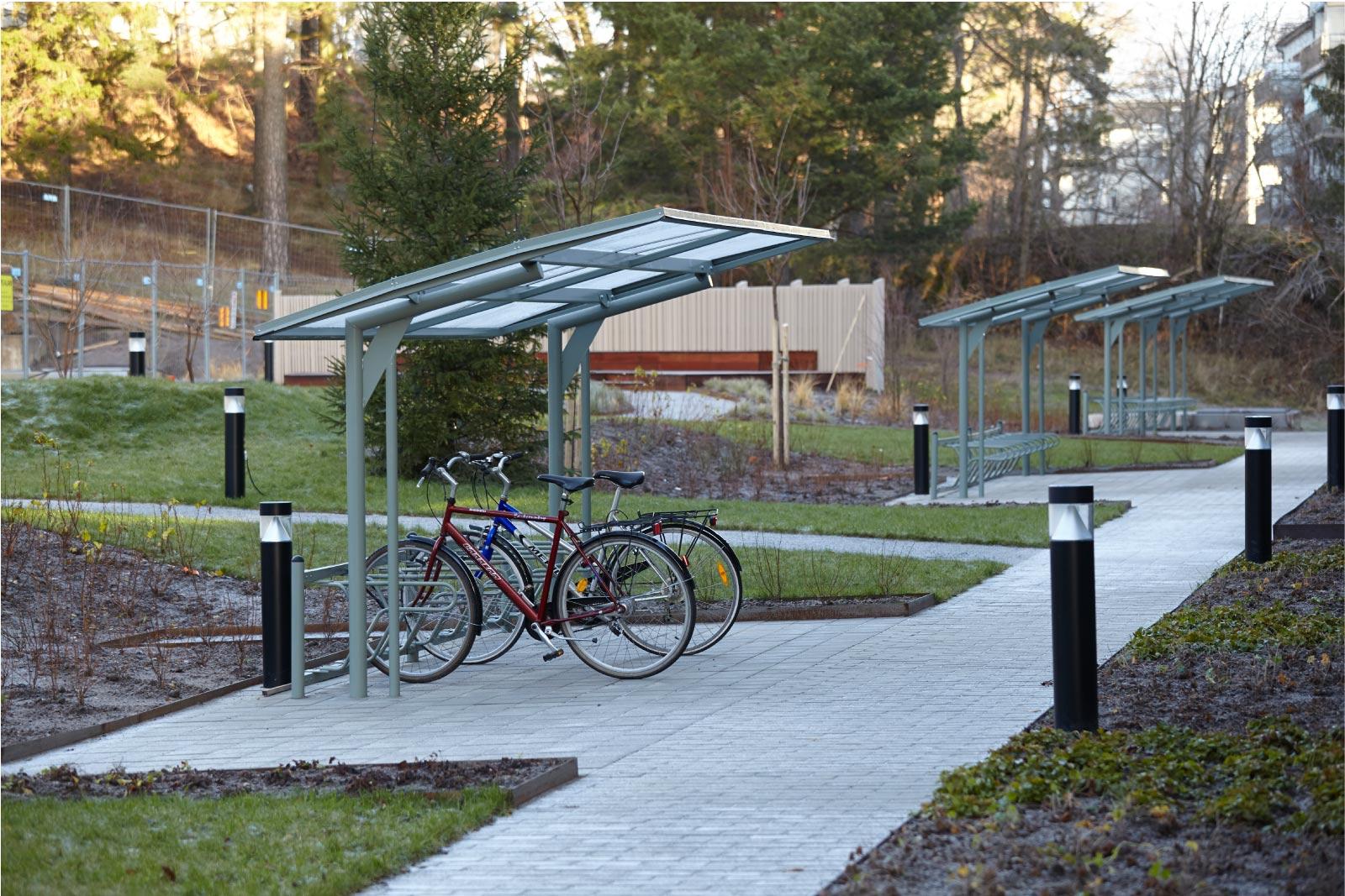 Cyklos KAPPA 5,5 metrin pyöräkatos, ilman päätytolppaa ja Delta runkolukitusteline, pyöräkatos taloyhtiönpihalla