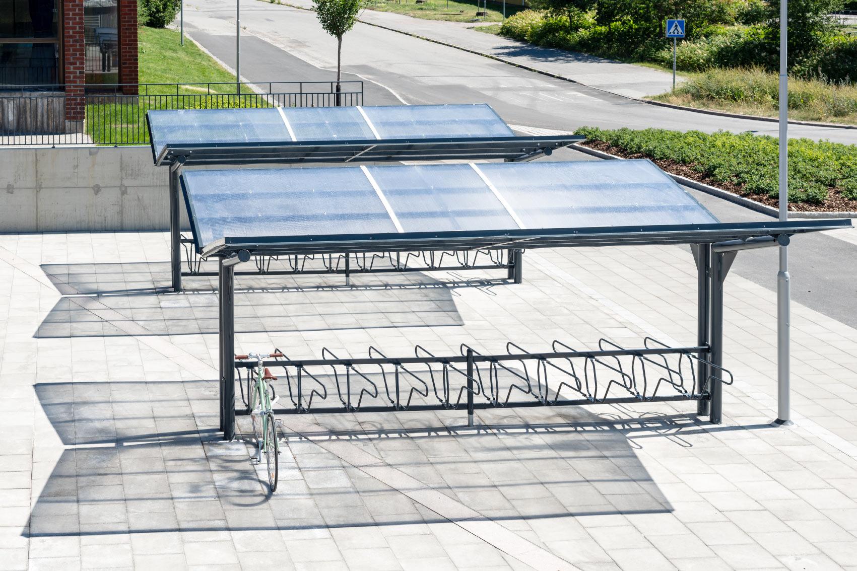 YPSILON Pyöräkatos sekä DELTA runkolukitus teline, muotoilu ja käytettävyys keskikössä, telineessä vihreä polkypyörä kiinnitetty runkolukolla
