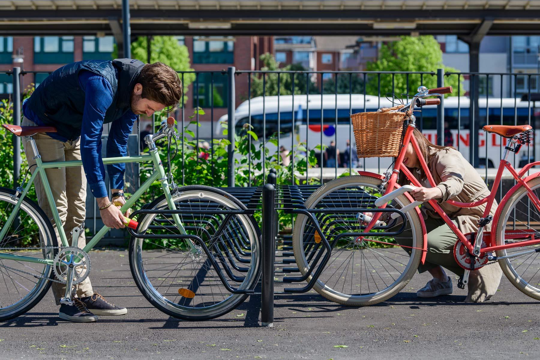 Pyöräteline johon kaksi pyöräilijää lukitsee pyöränsä runkoon