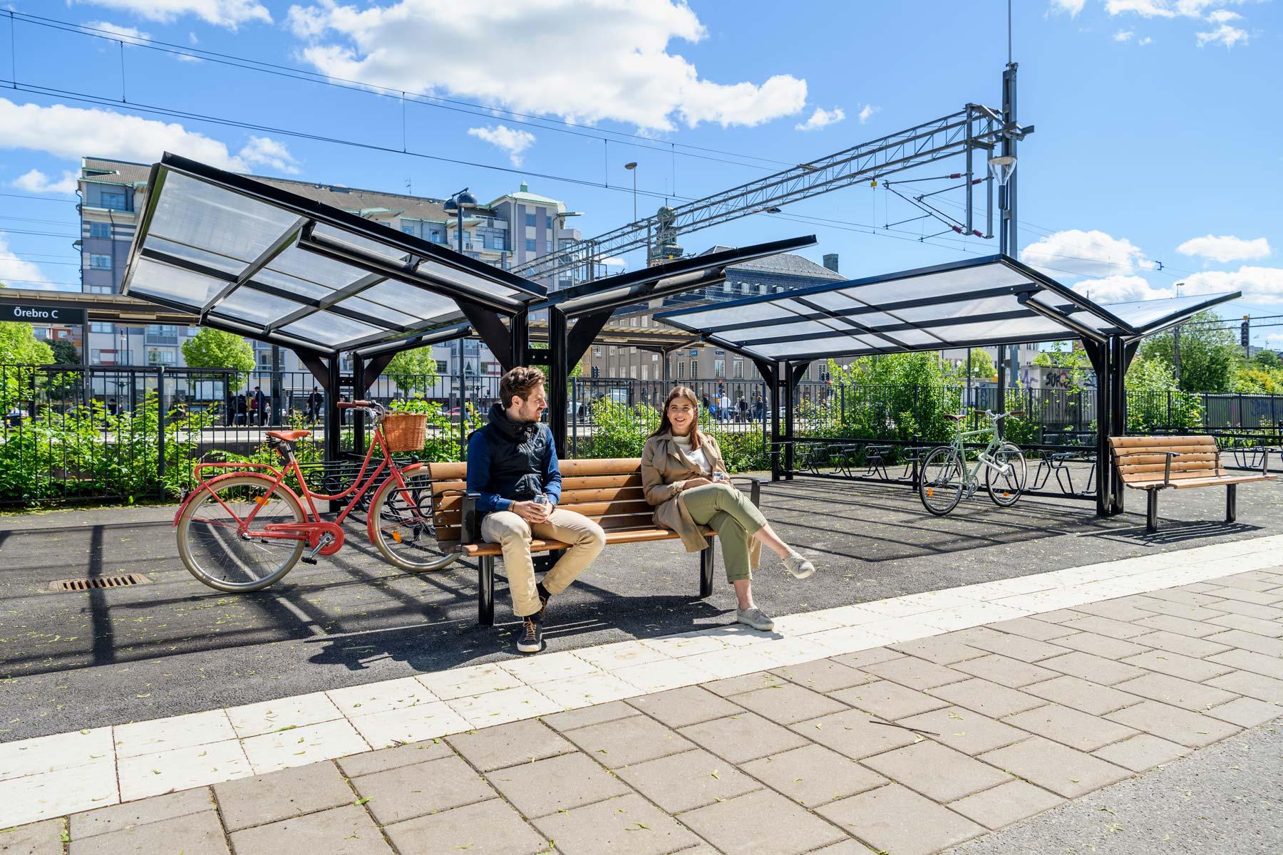 Kaksipuolinen pyöräkatos penkeillä, mies ja nainen istuu penkillä.