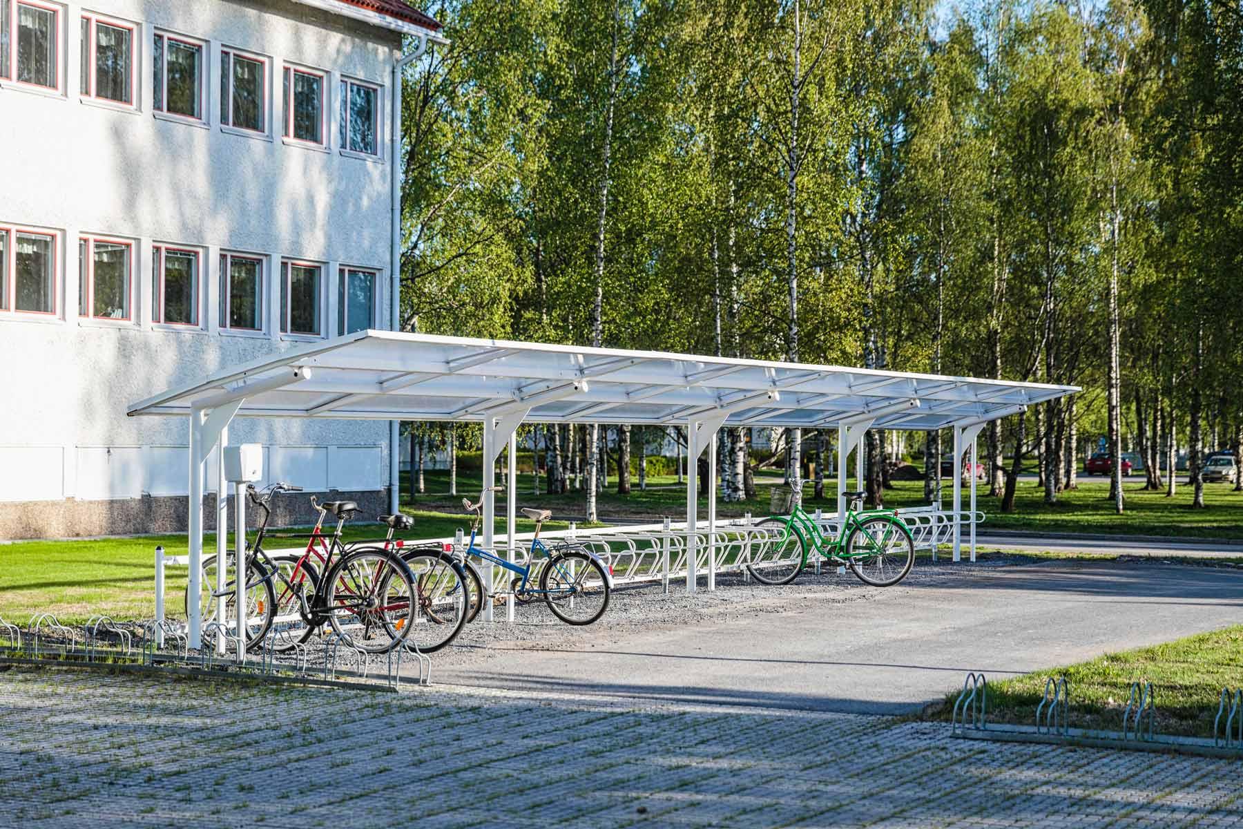 Valkoinen pyöräkatos koivujen vieressä