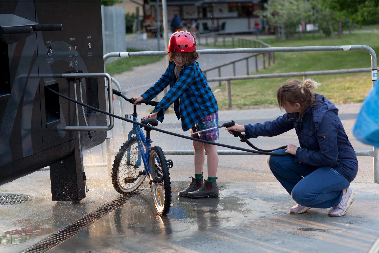 En kvinne og et barn renser sin sykkel på Sykkelservicestasjonen GRAND 3600
