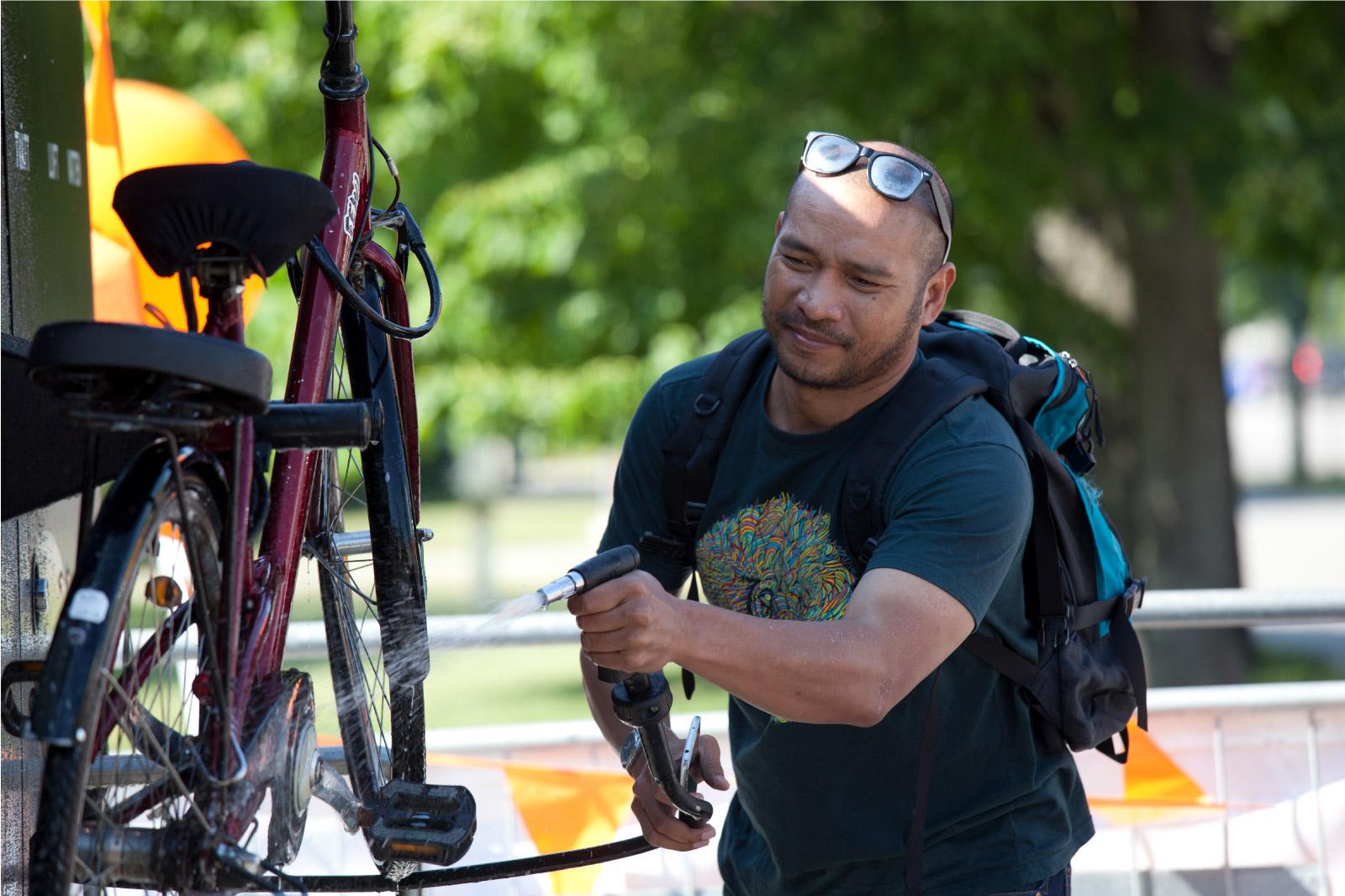En mann renser sin sykkel på Sykkelservicestasjonen GRAND 3600