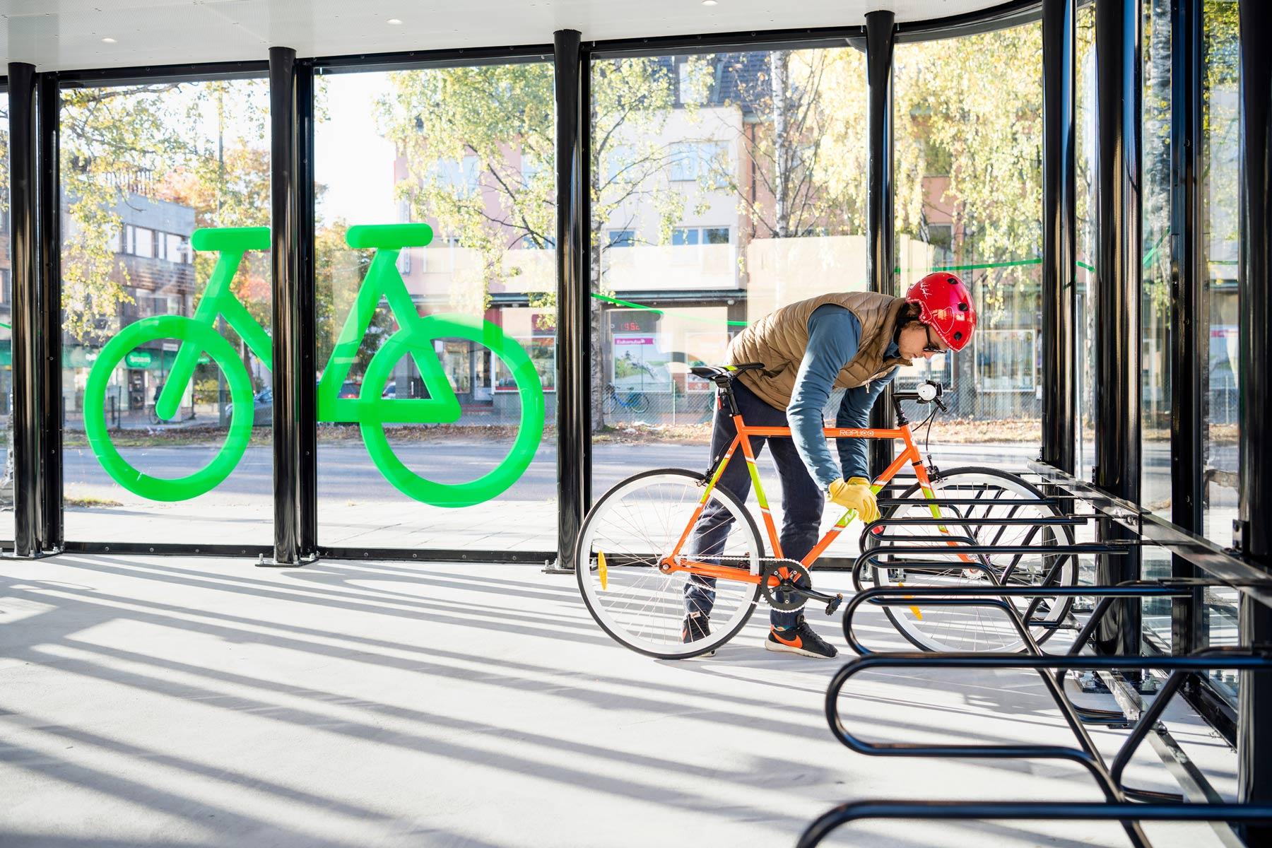 Sykkelhus FLOW i Umeå Sverige med runde hjørner, vegger helt i glass og sykkelstativ DELTA.