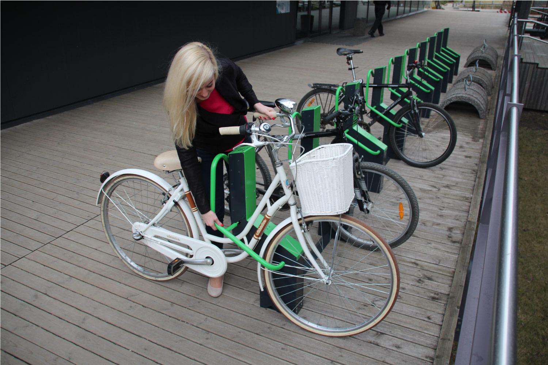Cyklist som låser fast en cykel på Cyklos cykelställ BIKEEP