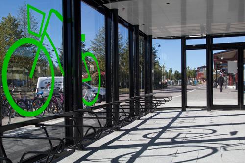 Cykelgarage FLOW med glasväggar, bild på grön cykel samt cykelställ DELTA på tågstationen i Katrineholm.