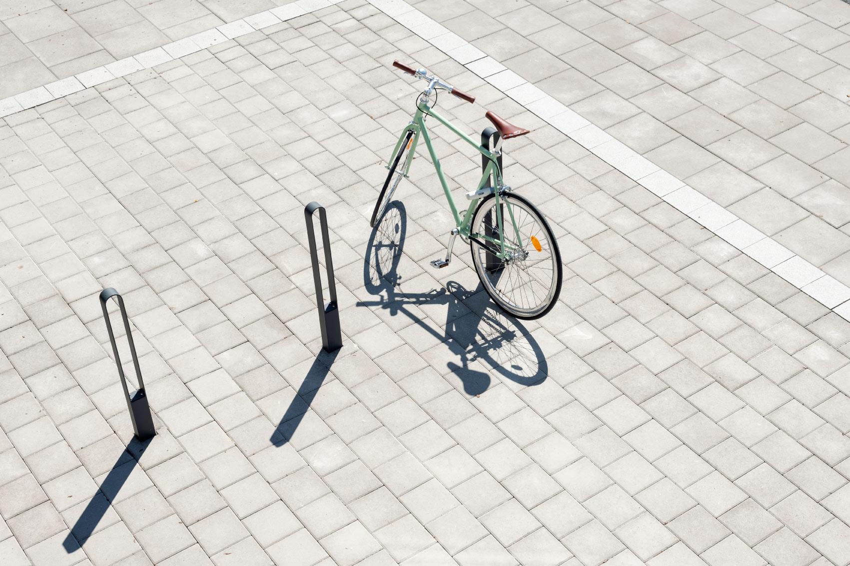 Cykel med sadel i läder parkerad och låst vid en av tre cykelpollare LUX från Cyklos