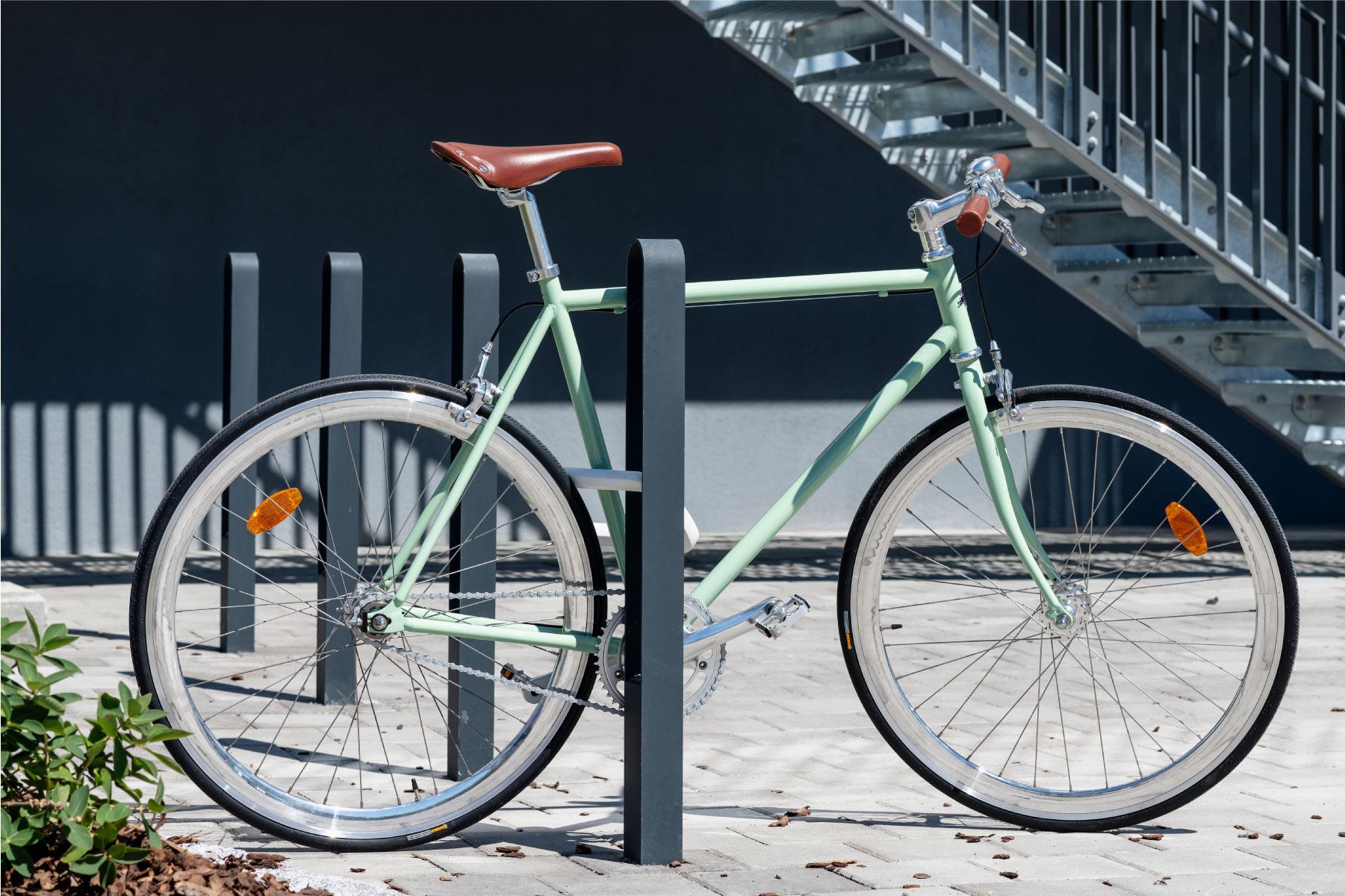Fyra cykelpollare LUX för offentlig miljö där det vid en av pollarna står en grön cykel