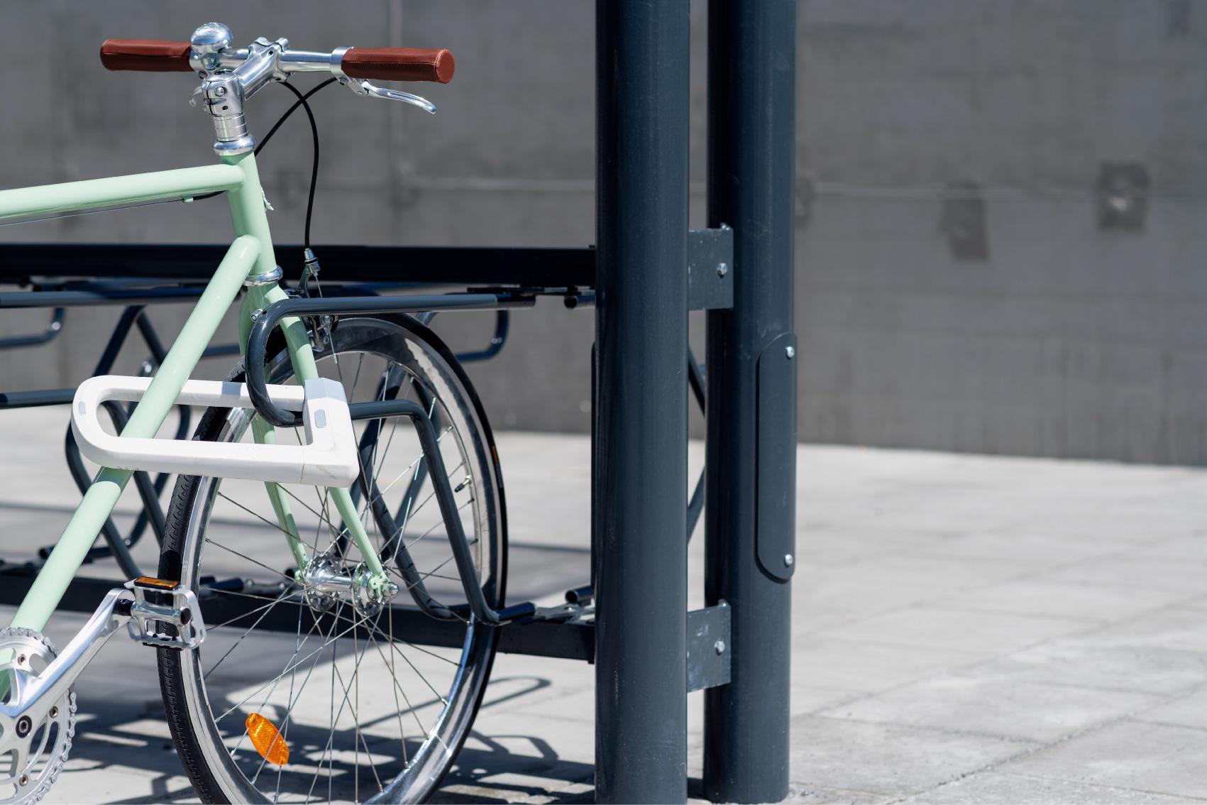 Grön cykel med läderhandtag som står i ett svart DELTA cykelställ från Cyklos