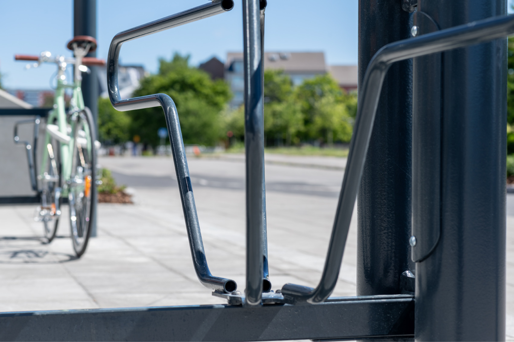 Detaljbild på DELTA cykelställ från Cyklos, i bakgrunden en grön cykel parkerad i cykelställ
