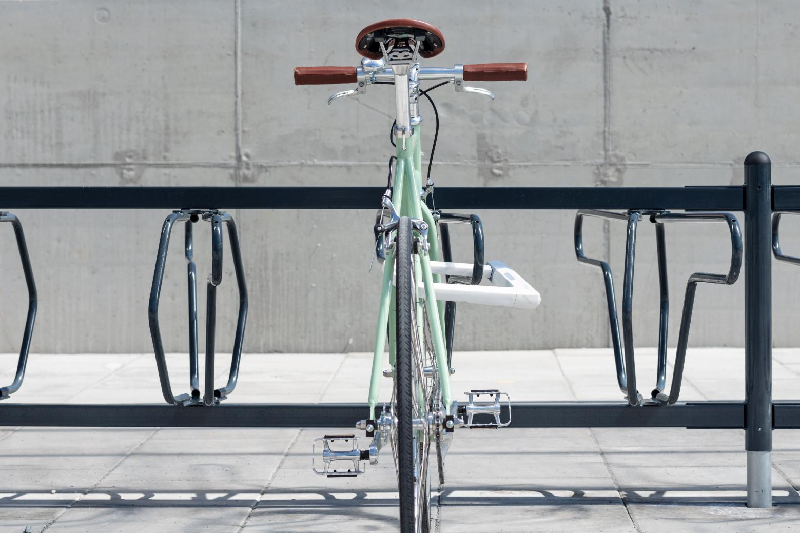 Grön cykel som står i ett svart DELTA cykelställ för offentlig miljö