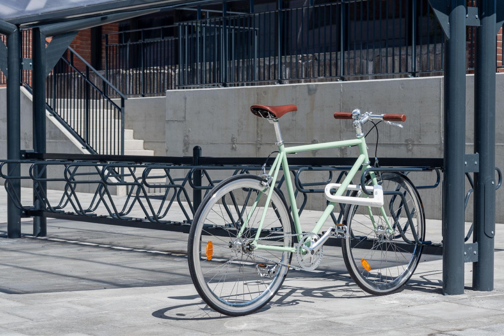 Grön cykel som är fastlåst i ramen i ett svart DELTA cykelställ för offentlig miljö