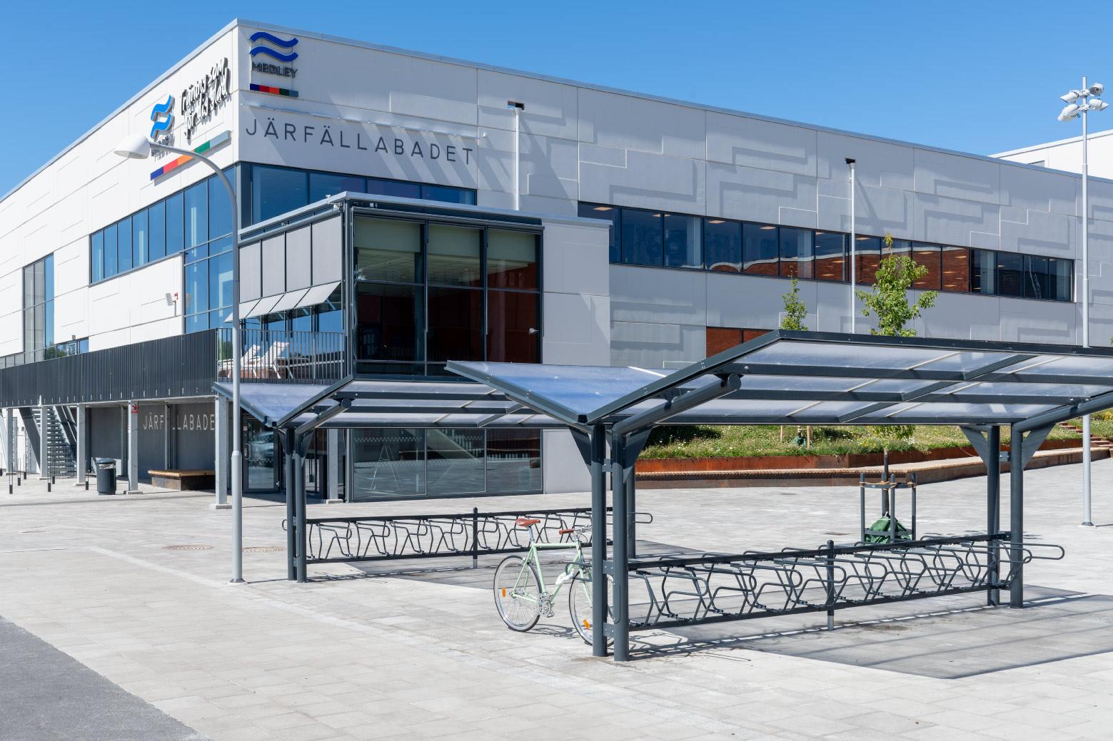 Dubbelsidigt cykeltak YPSILON från Cyklos utanför Järfällabadet i Järfälla tillsammans med cykelställ DELTA där en parkerad cykel är fastlåst i ramen