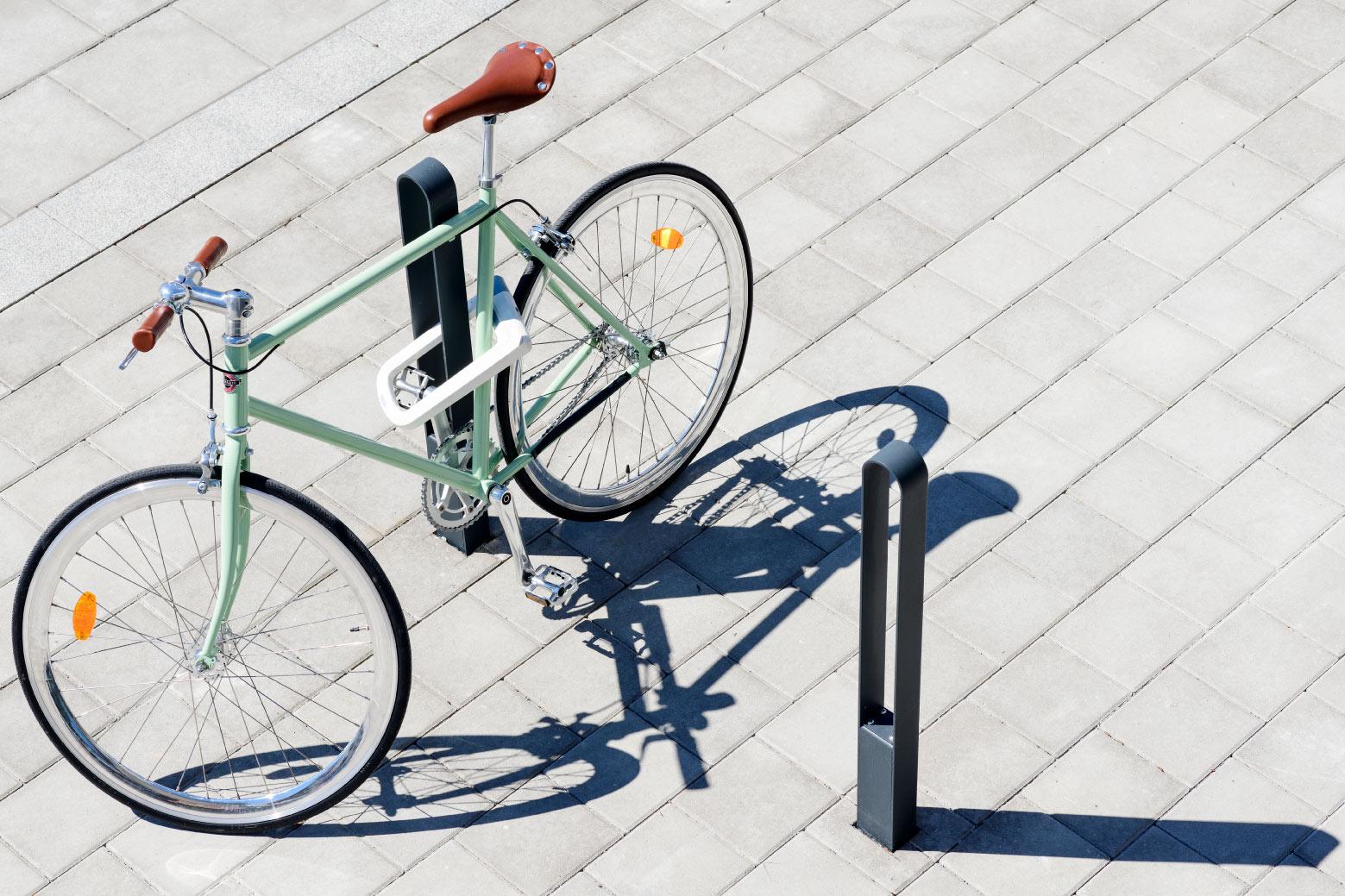 Två cykelpollare LUX från Cyklos där det vid en av pollarna står en grön cykel
