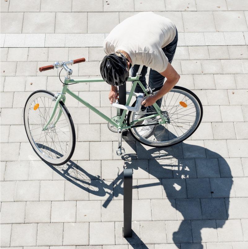 Cyklist parkerar en grön cykel vid en cykelpollare LUX från Cyklos