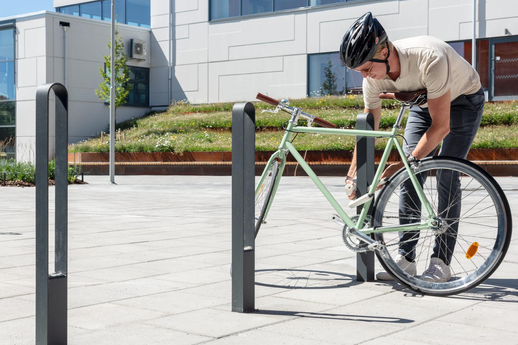 Cyklist låser fast en grön cykel vid en cykelpollare LUX från Cyklos