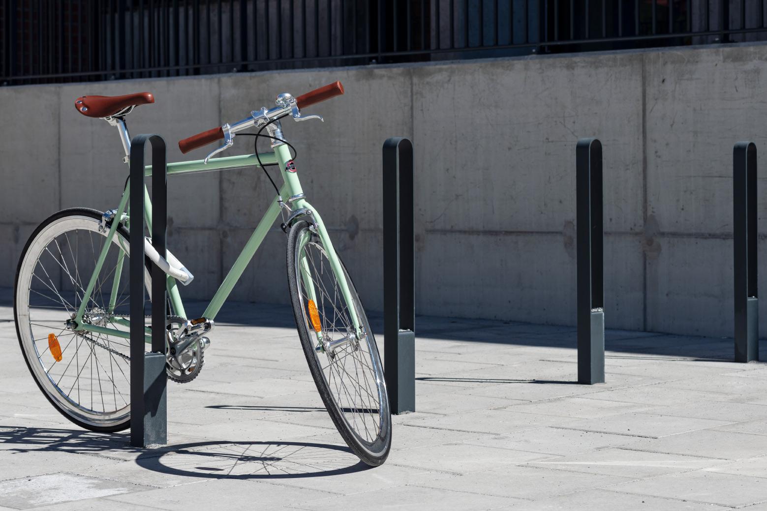 Fyra cykelpollare LUX från Cyklos där det vid en av pollarna står en grön cykel
