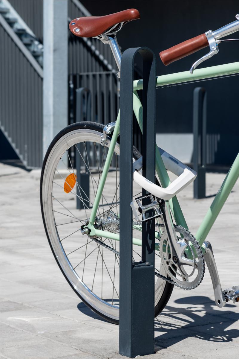 Cykelpollare LUX från Cyklos där en grön cykel står parkerad