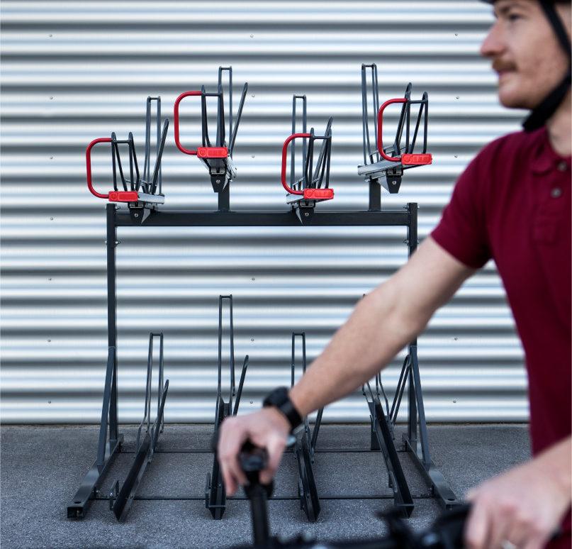 Cyklist lutar sig mot cykel, i bakgrunden syns tvåvåningsstället OPTIMA från Cyklos