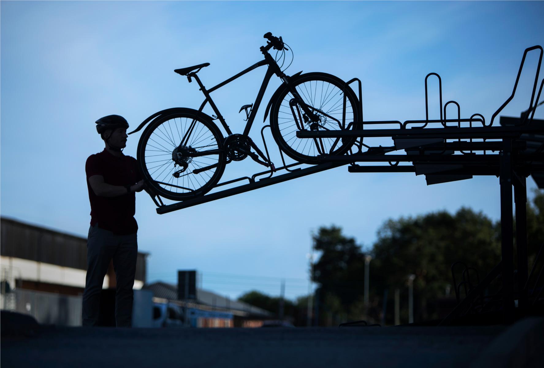 Cyklist i siluett parkerar sin cykel i ett tvåvåningsställ