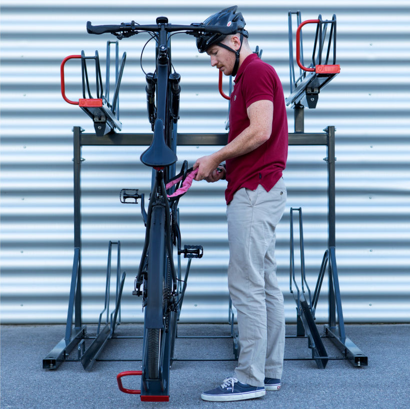 Cyklist låser fast en cykel i ett tvåvåningsställ för cyklar