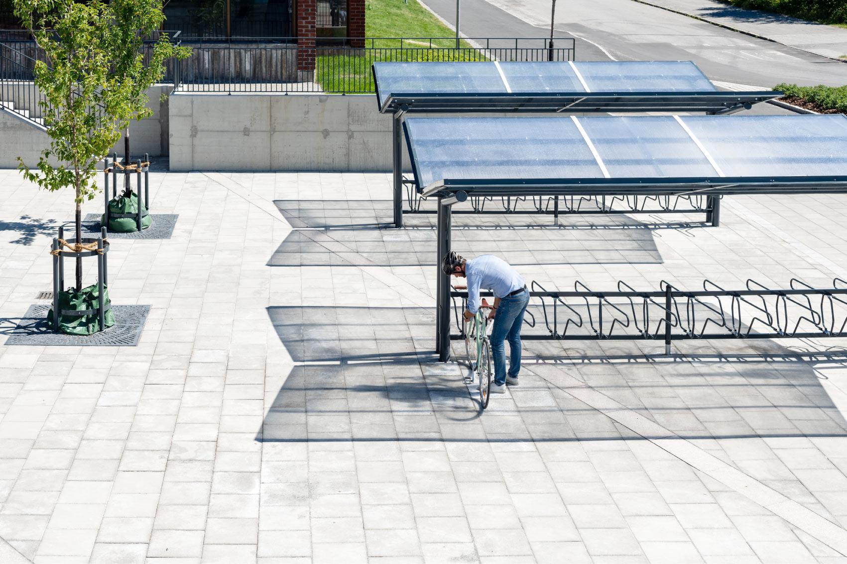 En cyklist låser sin cykel i det dubbelsidiga cykelstället DELTA under det dubbelsidiga cykeltaket YPSILON från Cyklos