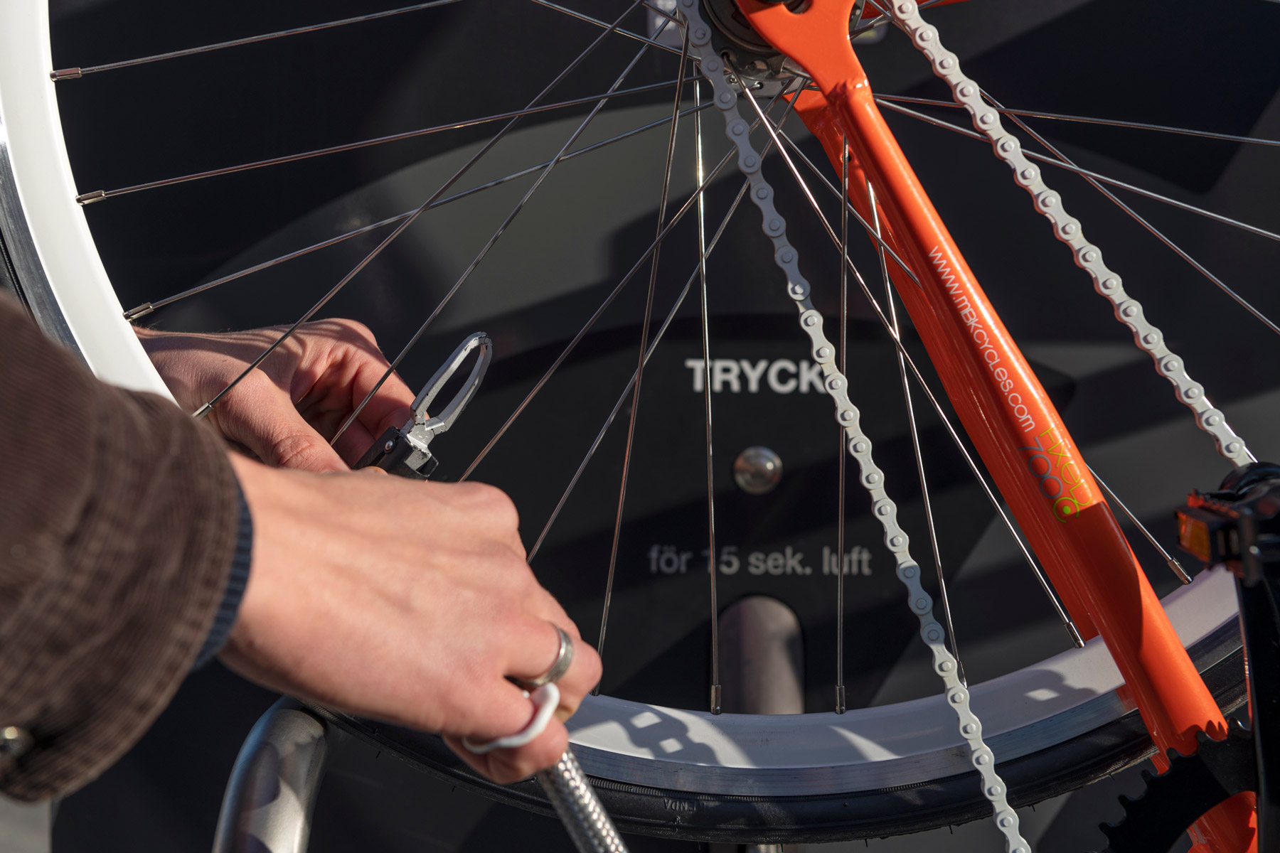 Cyklist fäster pumpmunstycket för att pumpa cykeln på cykelservicestationen GRAND från Cyklos