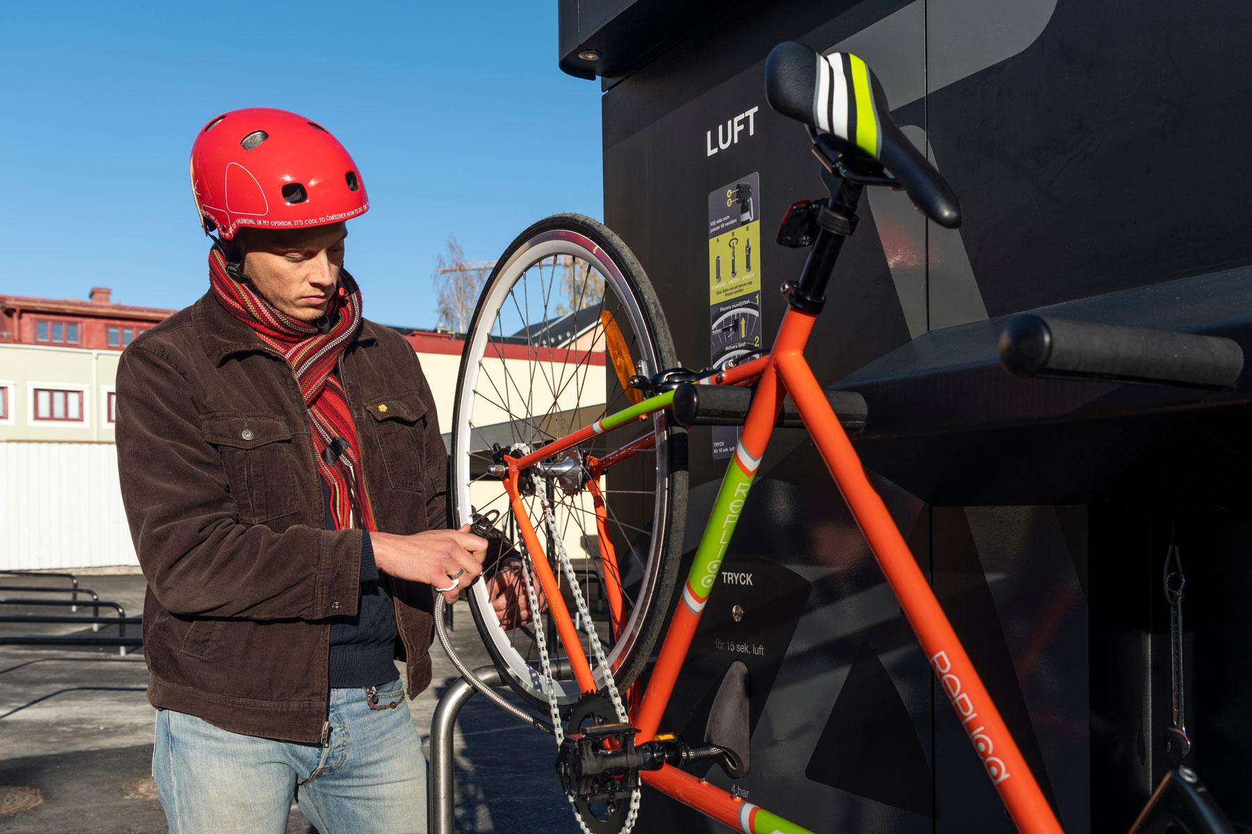 En cyklist i röd hjälm fäster pumpmunstycket för att pumpa cykeln på cykelservicestationen GRAND från Cyklos