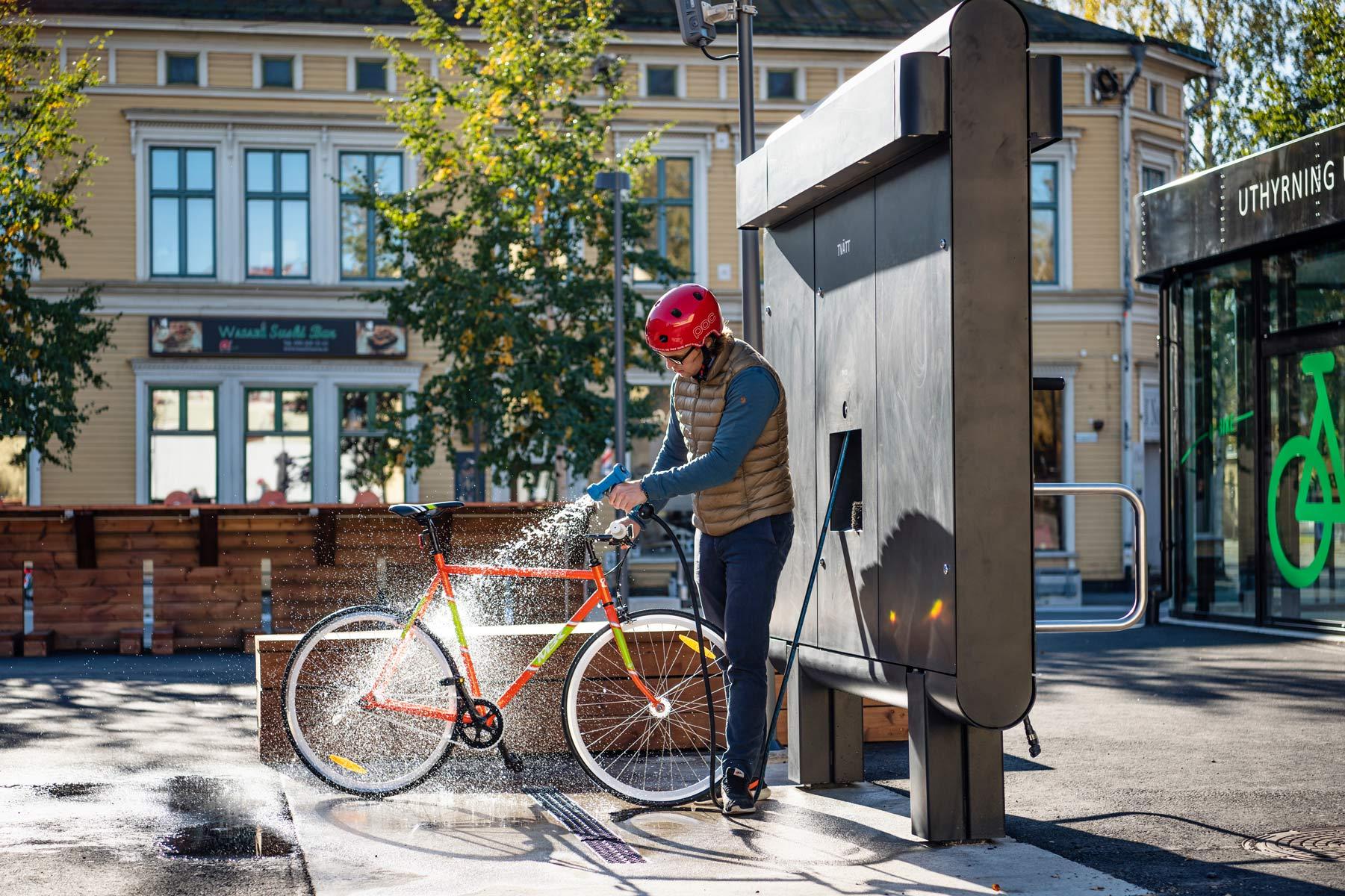 Cyklist i röd hjälm spolar av sin cykel med cykelservicestationen GRAND från Cyklos