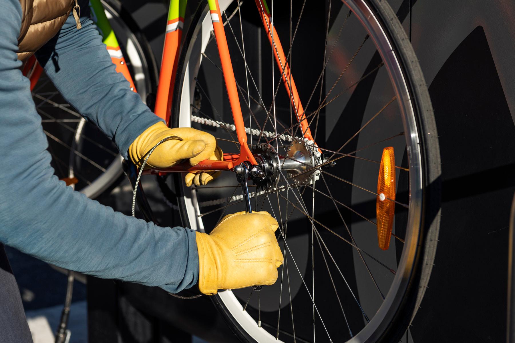 Cyklist med gula handskar använder verktygen på cykelservicestationen GRAND från Cyklos