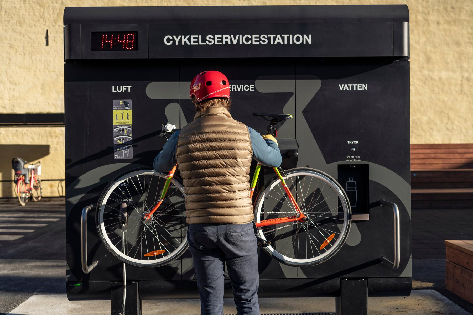Cyklist hänger upp sin cykel på en cykelservicestation från Cyklos