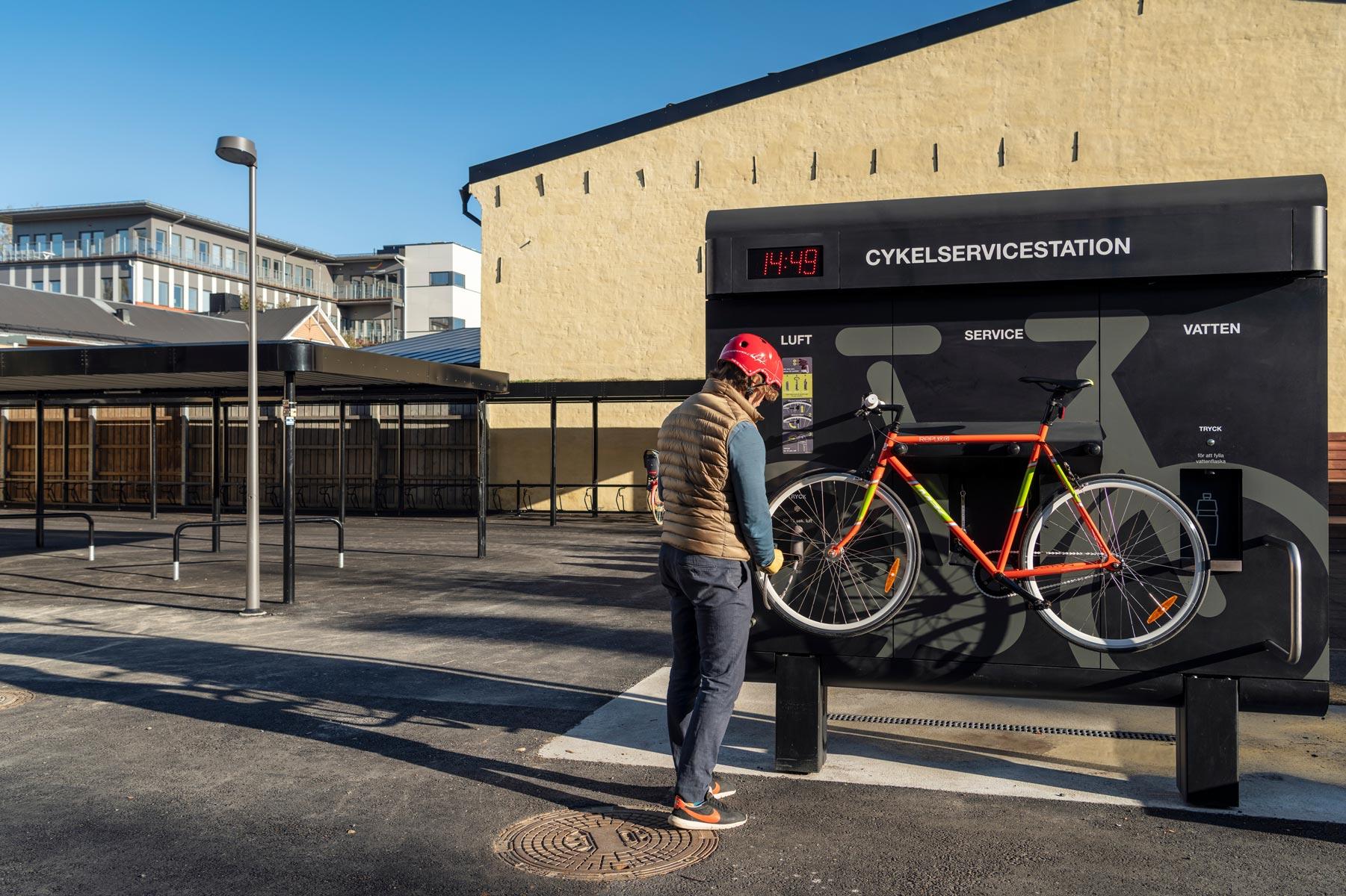 En cyklist pumpar däcken på sin rödgröna cykeln som är upphängd på cykelservicestationen GRAND från Cyklos