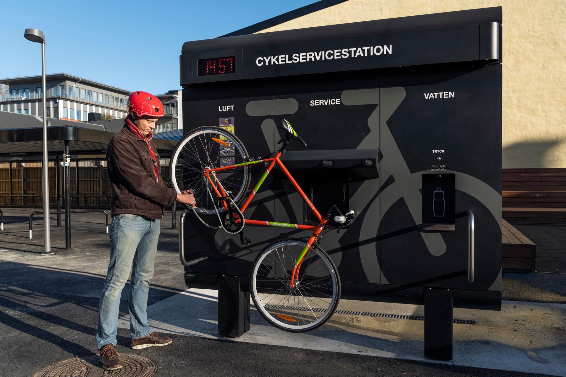 En cyklist i röd hjälm pumpar sin rödgröna cykeln som är upphängd på cykelservicestationen GRAND från Cyklos