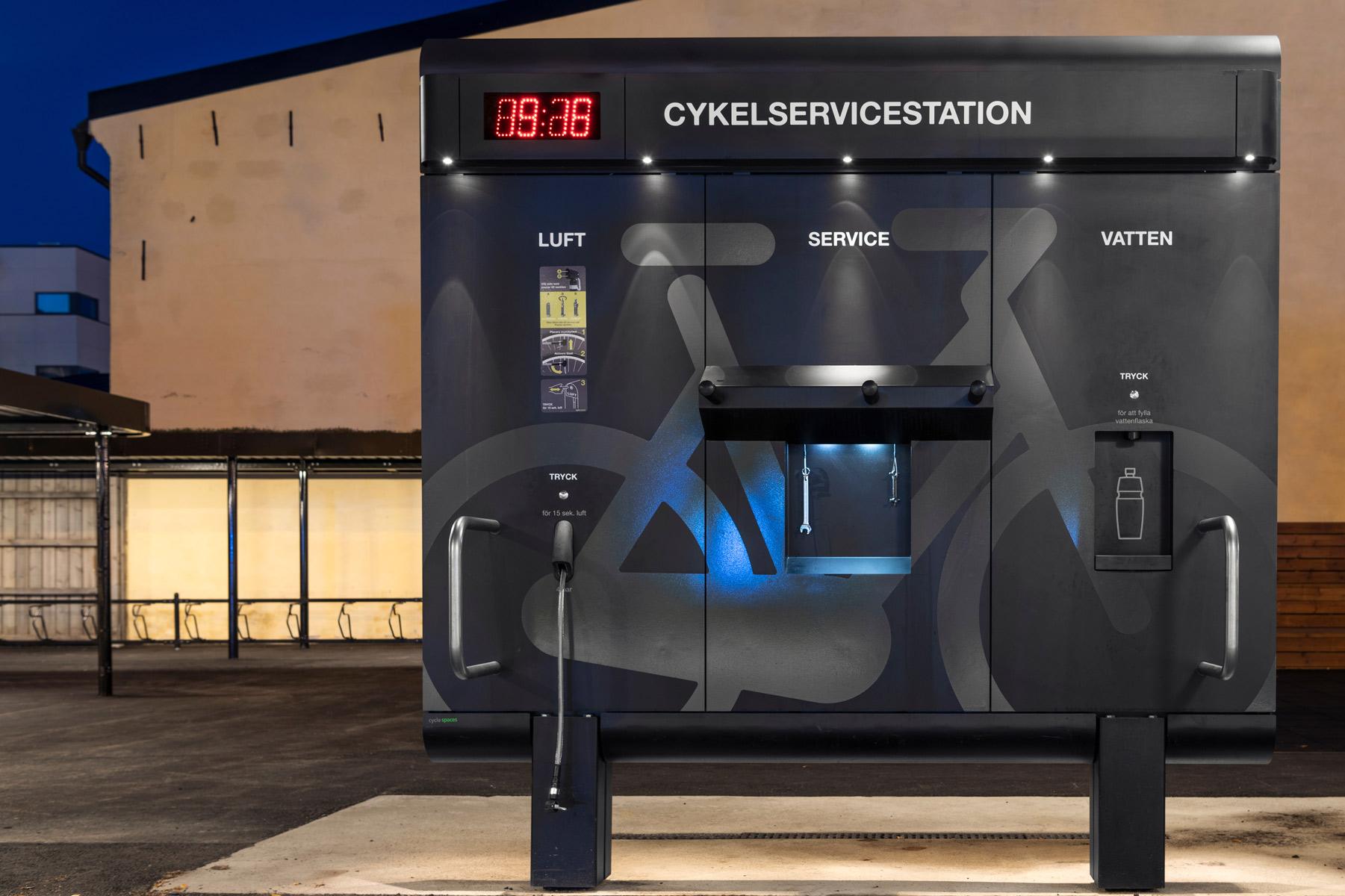 Cykelservicestation GRAND från Cyklos i skymningsljus, med LED-belysning, cykelpump, multiverktyg, påfyllning av vattenflaska och på baksidan en tvätt.