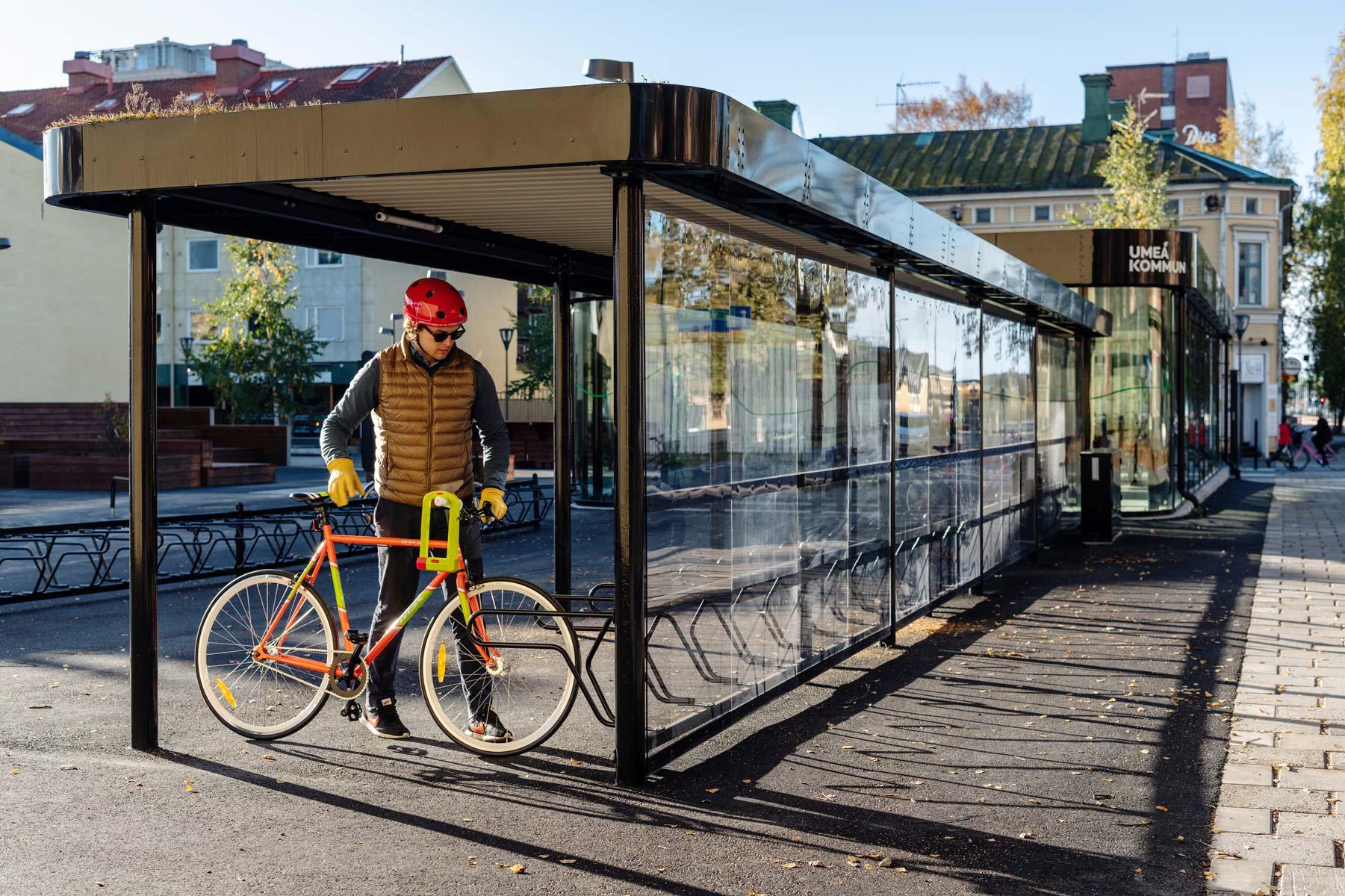 Cykeltak och cykelställ där cyklist parkerar sin rödgröna cykel