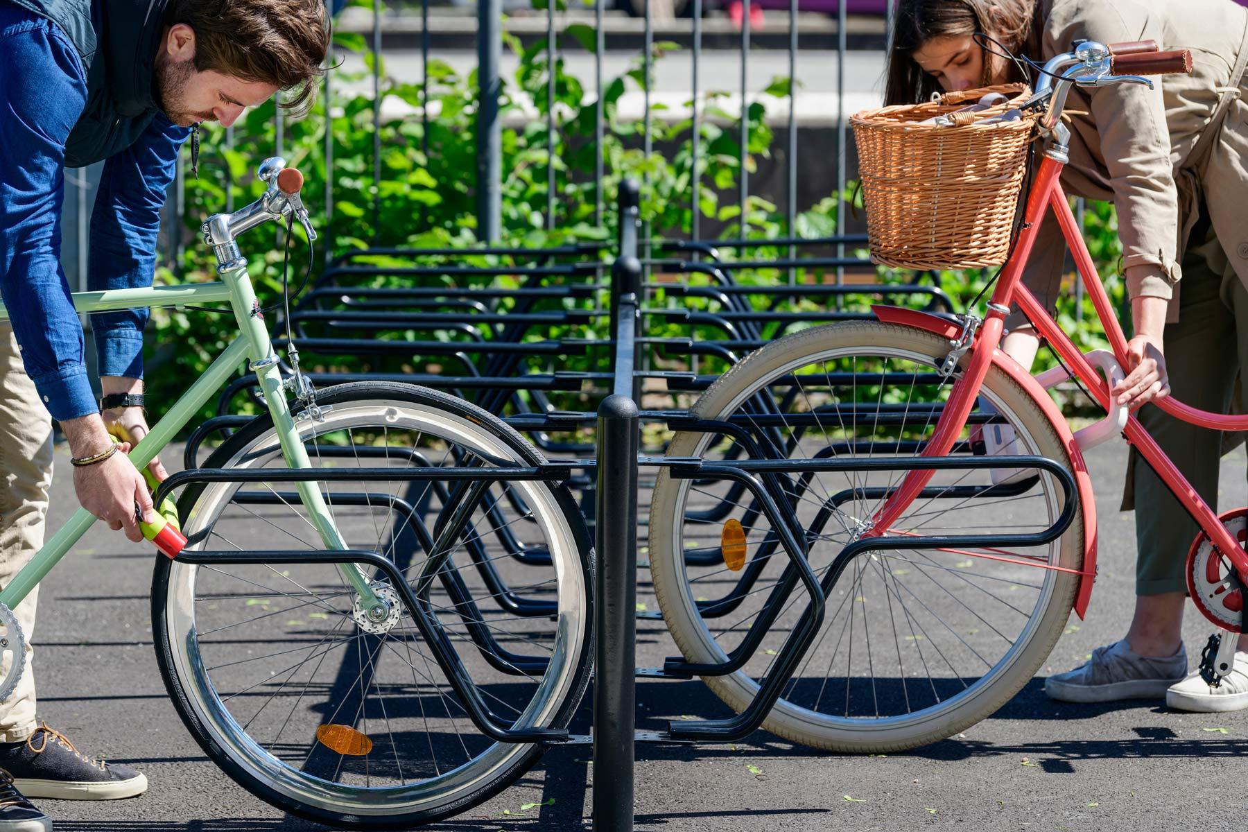 Cykelställ DELTA där två cyklister låser fast cyklarna i ramen