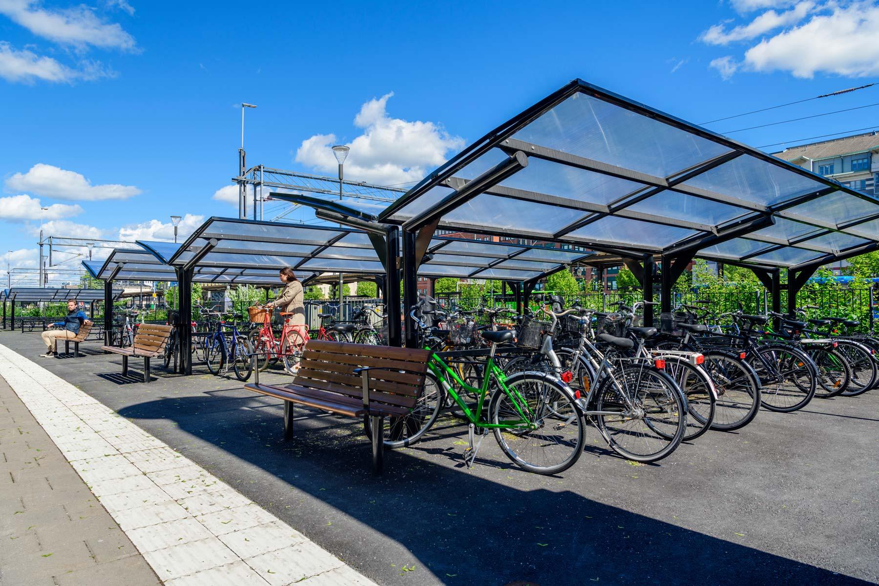 Dubbelsidigt cykeltak där en kvinna parkerar en cykel och en man sitter på en bänk.