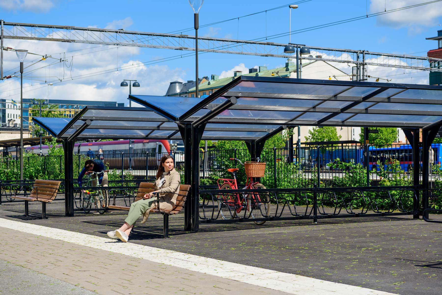 Cykeltak i dubbelt utförande och en parkbänk där en kvinna sitter.