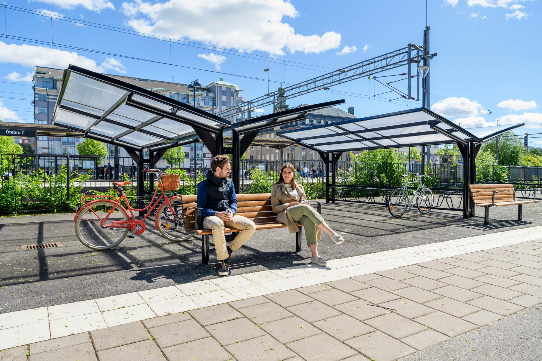 Dubbelsidigt cykeltak med parkbänk framför där en man och en kvinna sitter.