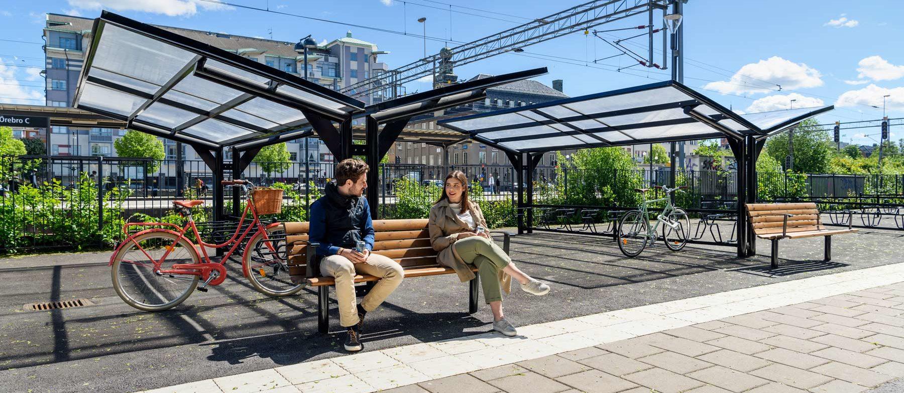 Cykeltak YPSILON med parkbänk och två studenter som pratar