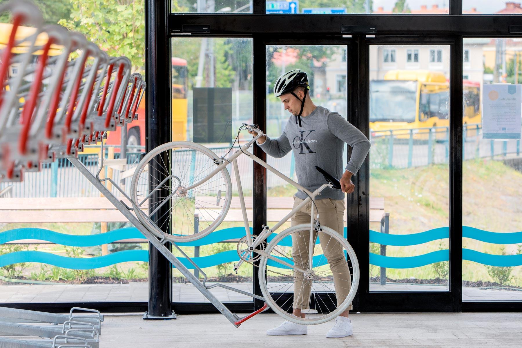 Cyklist som använder 2-våningsställ i ett cykelgarage
