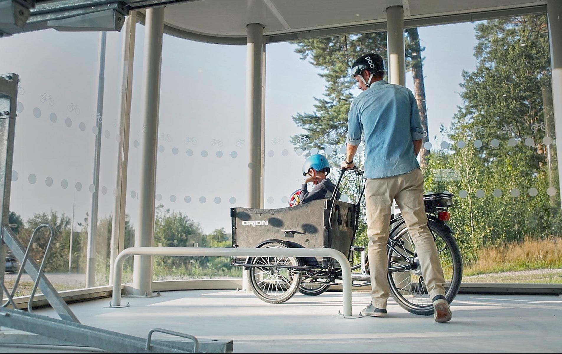 En pappa parkerar sin lastcykel vid en cykelparkering