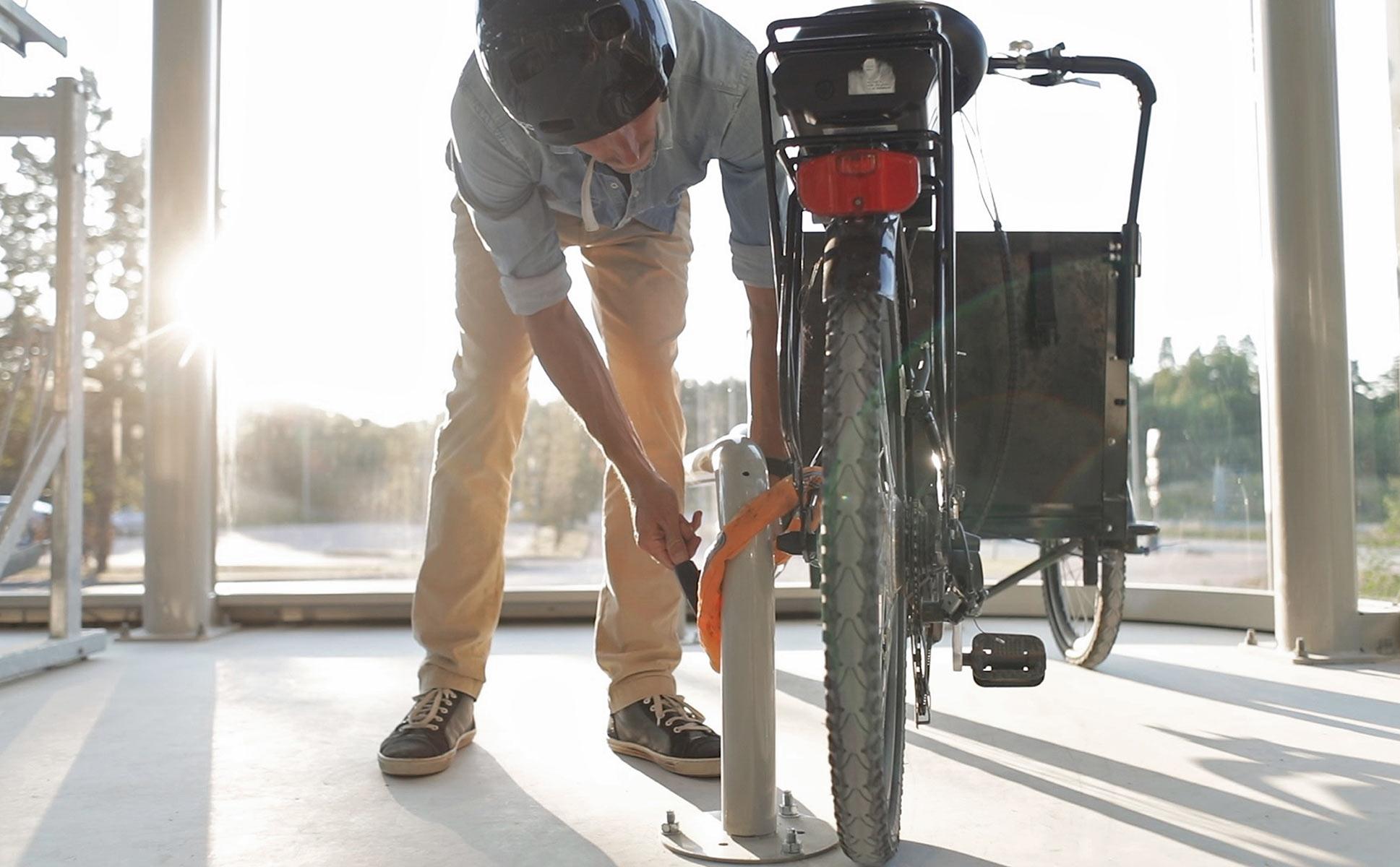 Cyklist låser lastcykel vid lastcykelparkering